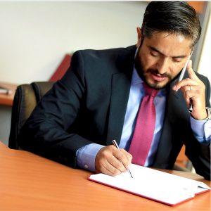 Commercial lawyer on phone writing